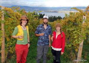 Kaylah Lewis (Gray Creek, BC), Brian McCloskey (French Village, NS) and Jolien Baeckelandt (Bruges, Belgium) - vineyard workers at Summerhill - take a break from picking grapes to toast the harvest with a glass of the young, still-fermenting wine.